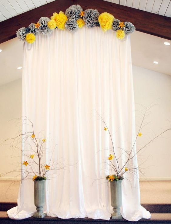 Tissue Pom Accented Backdrop / http://www.himisspuff.com/pom-poms-decor-ideas-for-your-wedding/6/