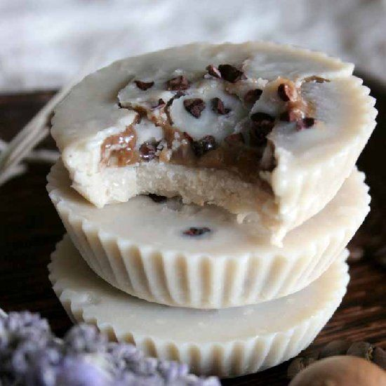 Tahini cups with coffee caramel filling topped with cacao nibs. Raw vegan dessert.