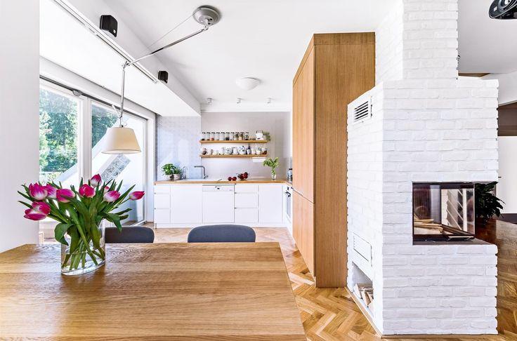 Osvětlení jídelního stolu zajišťuje ikonická lampa Tolomeo (Artemide), čalouněné židličky majitelka zvolila sama ve světle šedém odstínu. Za pracovní deskou je skleněná stěna s dekorem navrženým designérkou Markétou Fleischnerovou.