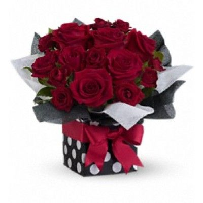 """Lush red roses in a sophisticated polka-dot gift box all tied up with a brilliant red ribbon. Innovative, imaginative, impressive - puttin' on the ritz with a touch of glitz! The ravishing bouquet includes red roses and red spray roses accented with fresh greenery. Delivered in a stunning polka-dot gift box with black and white water-resistant tissue paper set off with a bright red ribbon. Approximately 14"""" W x 12"""" H"""