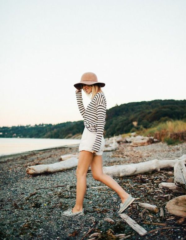 une femme marche sur la plage avec un chapeau de feutre
