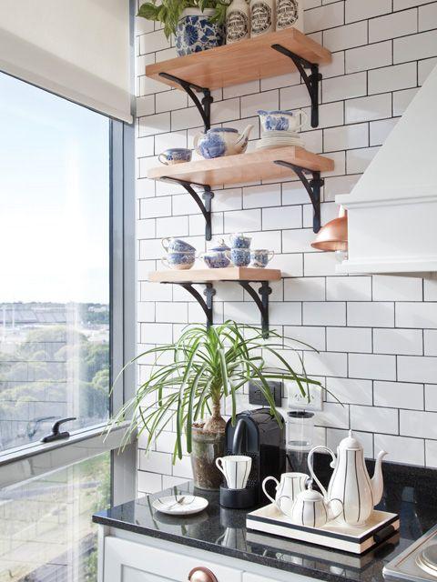 Cocina moderna en clave Nueva York: azulejos en blanco y juntas negras, artefactos en cobre, plantas, estantes de madera y acero, y juego de té a rayas. Foto: Magalí Saberian