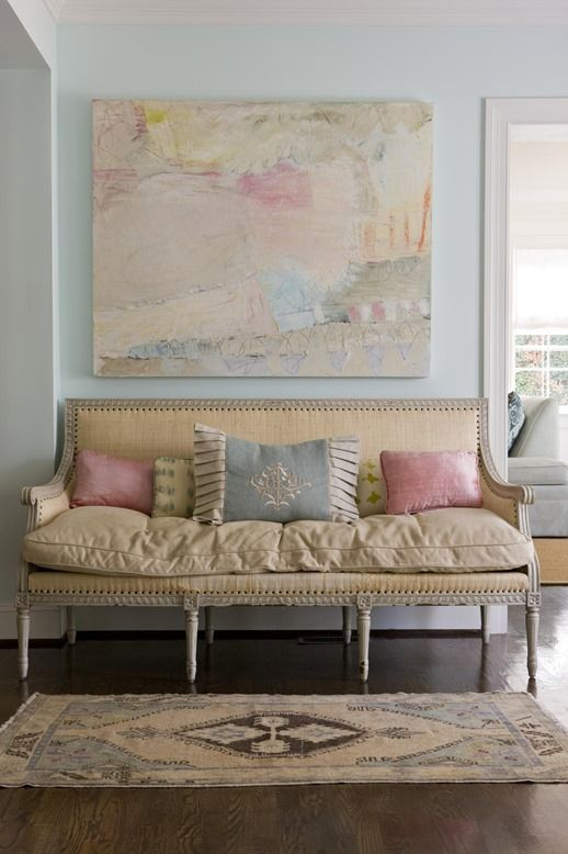 Oly sofa (like basement chairs) with pastel and sherbet colored pillows and artwork.