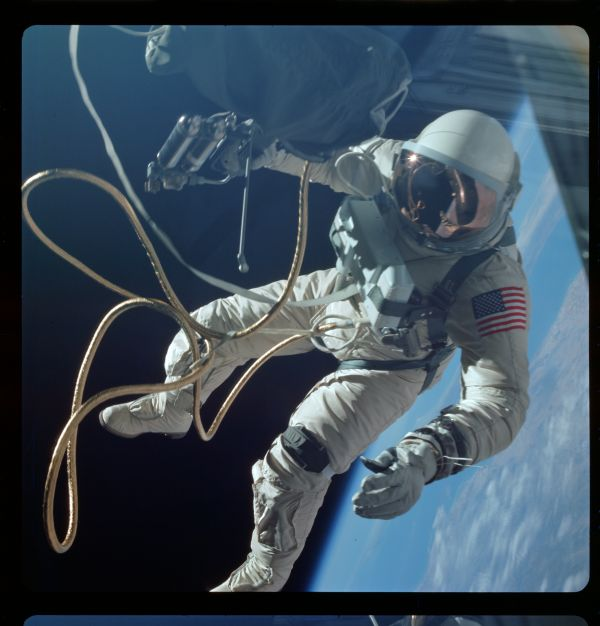 S65-30433_G04-H  Astronaut White floats in zero gravity of space over New Mexico. White is attached to the spacecraft by a 25-ft. umbilical line and a 23-ft. tether line,both wrapped in gold tape to form one cord. In his right hand White carries a Hand-Held Self-Maneuvering Unit (HHSMU). The visor of his helmet is gold plated to protect him from the unfiltered rays of the sun.