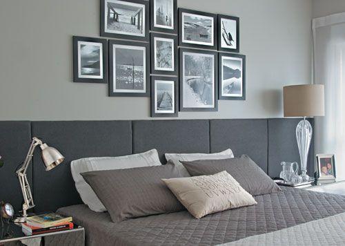 A parede cinza clarinha faz apenas um fundo pra cabeceira horizontal em tecido cinza chumbo e a composição de fotos e preto e branco. Via Casa Cláudia.