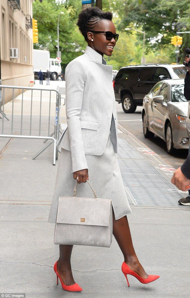Eye-catching: Lupita coupled her chic grey dress with a pair of standout, bright orange pu...