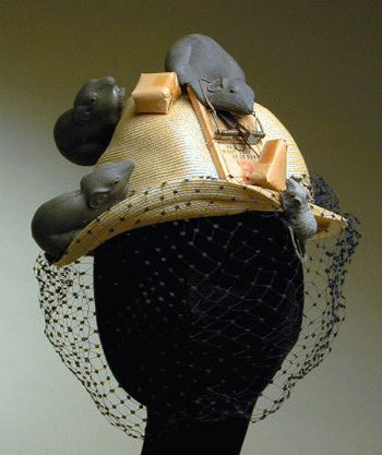 Bes-Ben 'Mousetrap' hat | Yellow straw, with high crown and narrow brim, decorated with three large gray rubber mice, one caught in wood mouse trap, the trap set with piece of cheese wrapped in brown paper, a baby mouse crawling up front of brim towards the trap | Made in Chicago, United States