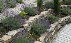 Zwei Mauern aus Natursteinen fangen den Höhenunterschied zum Garten ab. Dazwischen ist genug Platz für die Bepflanzung mit Lavendel