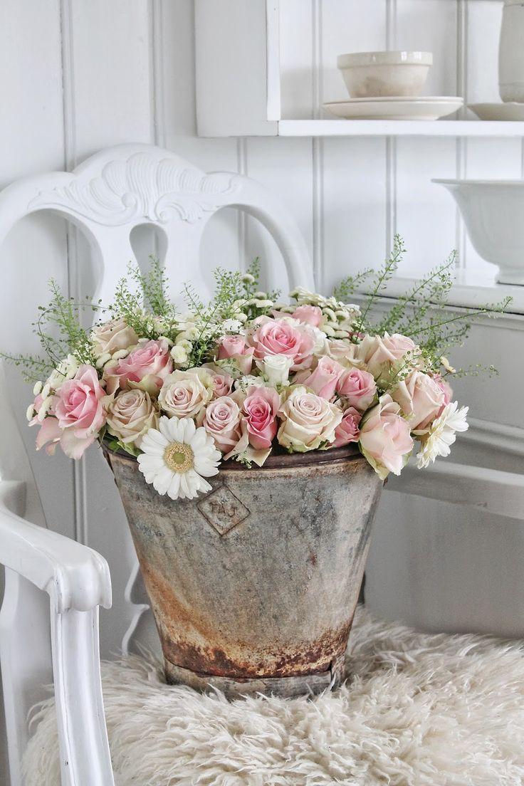 Roses and daisies in rustic metal bucket.