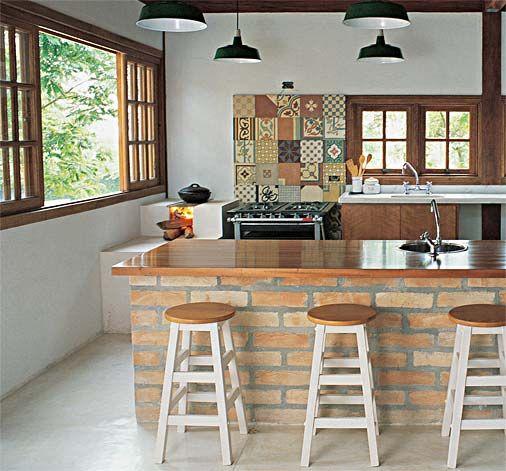 Cozinha com mosaico de ladrilho hidráulico, bancada de tijolo aparente e piso de cimento queimado.