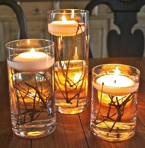 Fill glass cylindrical vases with water, put a few twigs at the bottom and float tea candles on top.
