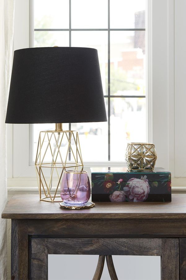 This chic black and gold table lamp reads like a piece of elegant jewellery on a little black dress. Simple amethyst glassware adds a delicate note.
