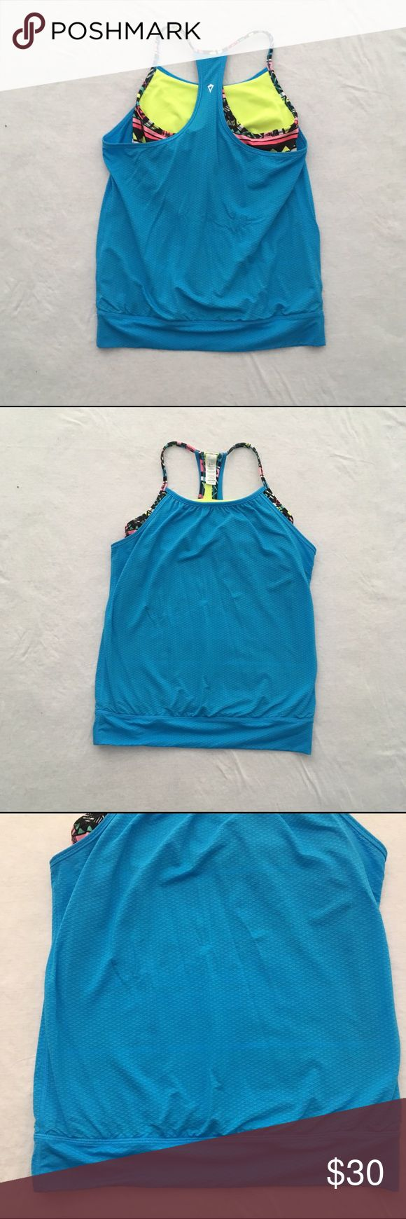Ivivva Double Dutch Tank Double Dutch tank by Ivivva. Exposed sports bra attached to the tank. Sports bra has spots for removal cups (not included). Great condition. No rips or stains.  Measurements (approximate, taken laying flat): Length: 22.5 inches  Material: Body: 89% nylon 11% Lycra spandex Contrast: 94% polyester 6% Lycra spandex Lining: 56% polyester, 33% coolmax polyester, 11% Lycra spandex Exclusive of trim  ❌No trades❌ Ivivva Shirts & Tops Tank Tops