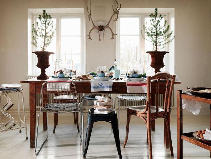 """I år är det naturlig jul som gäller. Det blir naturfärger som grönt, brunt och mycket trä. Med temat """"naturligt"""" blir det förstås också mycket naturgodis som nötter och äpplen. Mycket av rekvisitan kommer från den egna tomten och skogen. Det dukade bordet väntar på gästerna. Rumsgranar står i rustika järnurnor som tagits in från trädgården.  Bordet är ett loppisfynd, likaså Thonetstolarna och de kromade metallstolarna. Tolixpall från Fil de Fer i Köpenhamn. Renhornetkommer från en skrotbod."""