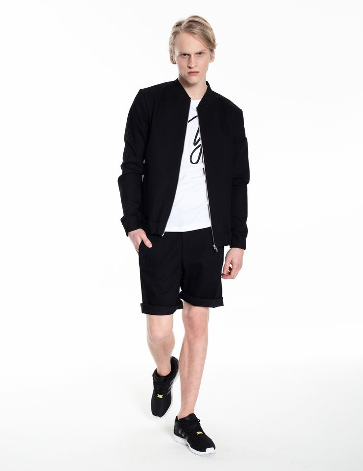 Model is wearing a black jeans set: bomber jacket and Universum shorts