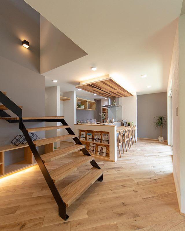 階段越しのダイニング キッチン脇にマガジンラックをin グレーの壁