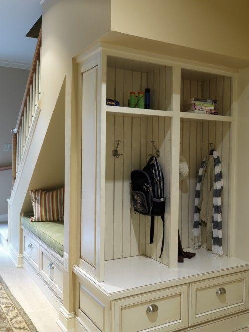 Organisation d'un espace de rangement pratique avec banquette sous un escalier.