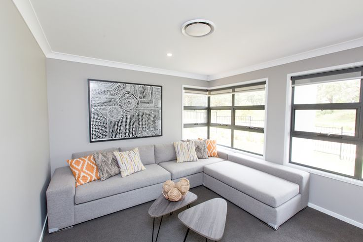 Medium grey carpet, light grey walls, white skirts, cornice and ceiling, charcoal or black window frames... it all works together and the orange scatter cushions provide the pop of warmth to stop it feeling clinical or cold.