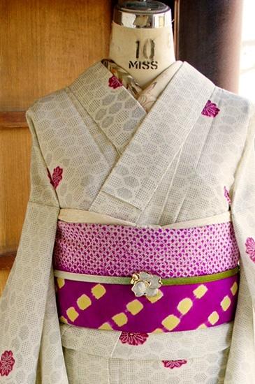 蚊絣のような繊細な十字でデザインされた亀甲模様がタイルようなモダンデザインを描き出す、クリームがかった自然な白色の地に、ふわりふわりと浮かぶように染め出されたフランボワーズレッドのお花模様が愛らしいサマーウールと思われる単着物です。