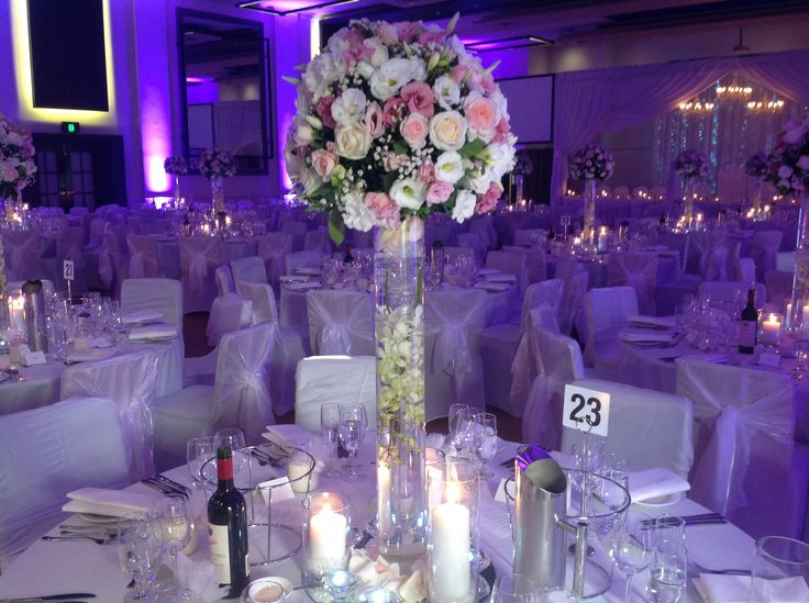 Singapore orchids submerged in a 90cm tall vase with fresh flower arrangement on top. www.houseofthebride.com.au