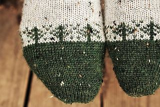 Simple, little evergreens march in fair isle across the contrast-color toe of the Charlie socks. Add to this an easy triple-wedge heel, striped cuff, and a gorgeous tweed yarn, and you have a perfect sock for hiking a wooded trail or lounging by a crackling fire! Sized for you to knit for guys and gals.