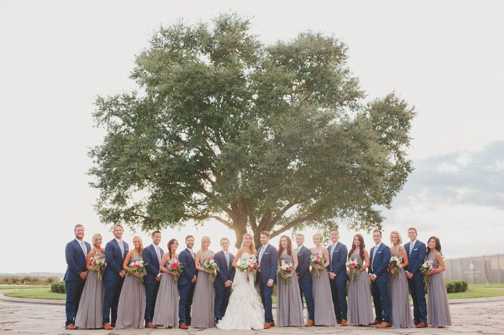 under a summer sky, groomsmen in navy suits and bridesmaids in grey gowns gather with the bride and groom in the shade of a florida live oak tree.