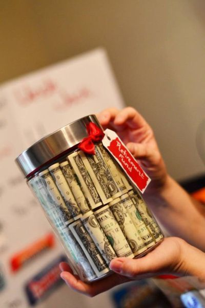 Fifty one dollars bills rolled up and stacked inside a clear jar.  See more 50th birthday gift ideas and party ideas at www.one-stop-party-ideas.com: