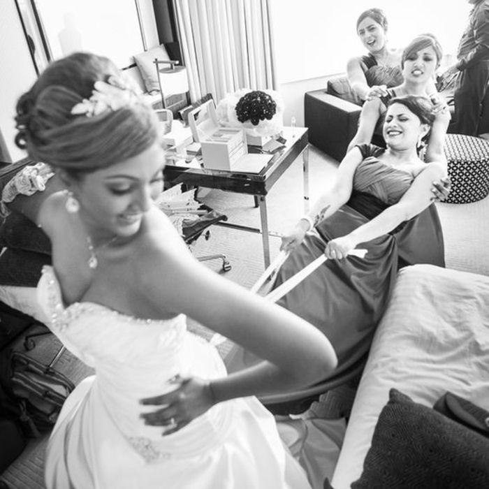 das Hochzeitskleid anziehen mithilfe der Brautjungfer