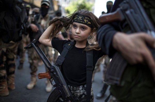 Een Palestijns meisje met een Kalasjnikov geweer, te midden van de islamitische Jihad militanten in Gaza-stad. Foto: Wissam Nassar for The New York Times