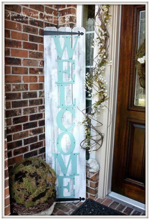 There's no better way to welcome guests to your porch than with an oversized pallet sign propped up next to your front door.