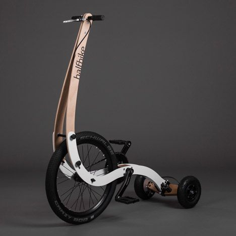 """""""Half bike II"""" by Kolelinia (2015) - photo from dezeen;  """"Halfbike II users stand up while peddling, shifting their bodyweight left or right to change direction while holding a vertical handle."""" This second version has a curved frame and """"the handlebar now sits above the front wheel rather that connecting to a frame at the cog axis."""""""