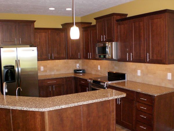 Note cherry wood cabinets light granite and gold wall for Kitchen cabinets and countertops ideas