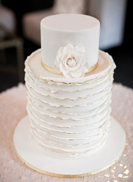 White wedding cake with gold edges.