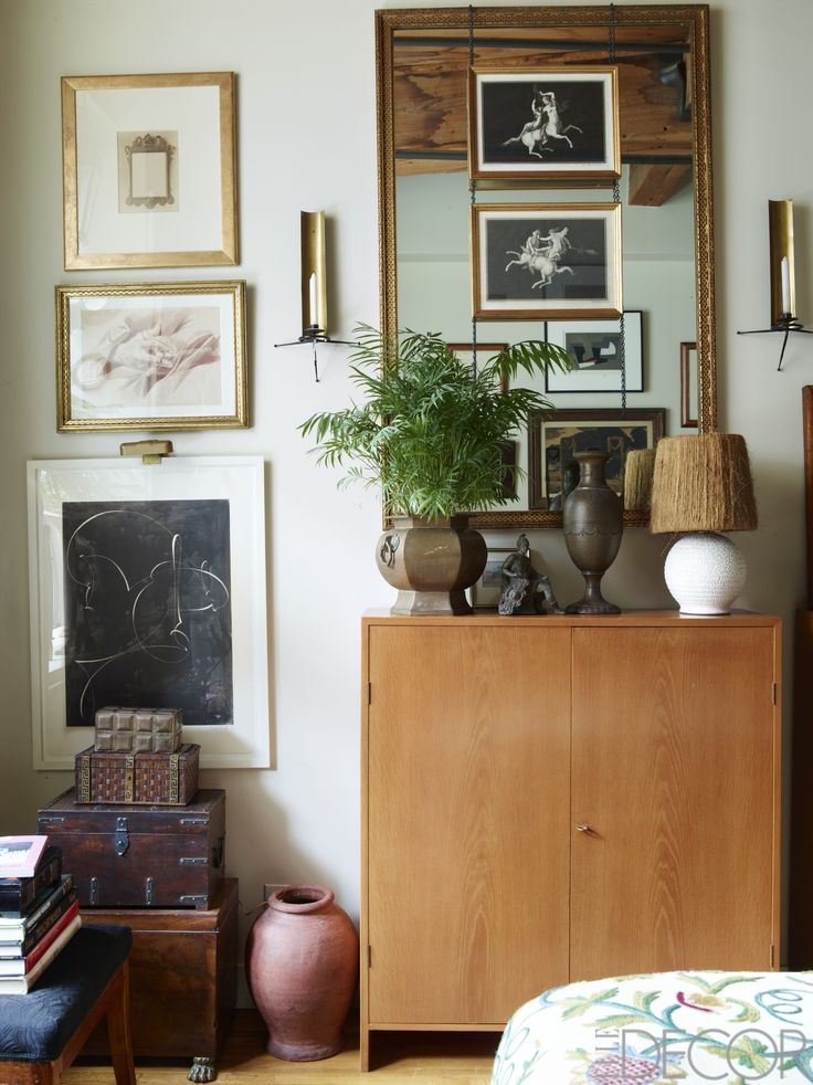 A flea-market mirror hangs above a cabinet by Hans Wegner in the bedroom. The sconces by Tony Paul were bought on eBay, and the large black-and-white print is by Elliott Puckette.   - ELLEDecor.com
