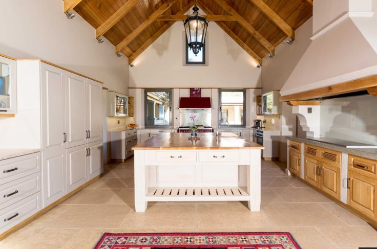 """The open plan kitchen / diningroom area. The large island is solid wood with a french oak top.  Double volume spaces with solid wood ceilings and high quality finishes complete the picture.  This area is part of the """"barn"""" in the farm house."""