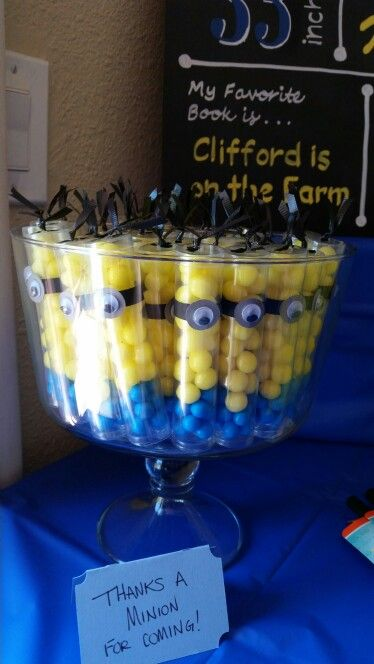 Minion candy favors for Despicable Me themed birthday party. Clear gumball tubes filled with colored candy and decorated to look like minions.