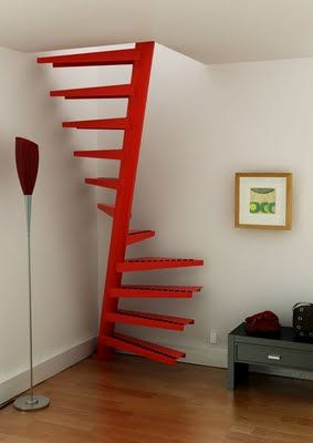 Super-compact cadmium red spiral staircase. EeStairs,  1m2® Staircase.    This staircase creates very strong lines against the stark white walls adding a very graphical element to the space. The bright saturated red brings life to this otherwise dull corner.