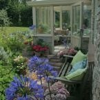 A small conservatory on the back of a Cotswold stone and timber clad cottage