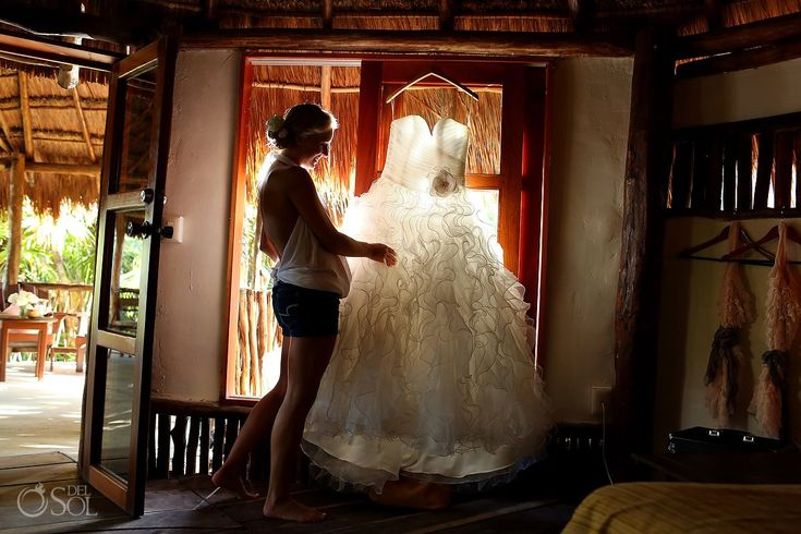 A destination wedding bride admires her gown by @Mori Lee by Madeline Gardner  in her cabana in Tulum at Nueva Vida de Ramiro. Mexico wedding photographers Del Sol Photography.