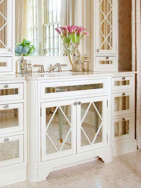 Feminine Chic Mirrored cabinet fronts create a glamorous style statement in any bathroom. This furniture-style vanity gets yet another boost of drama from mirrored fronts outfitted with delicate trim in a classic diamond pattern. The cabinet fronts reflect the room's natural light and unite subtle patterns featured elsewhere in the room.