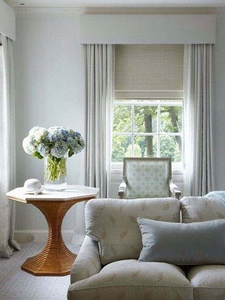 Calm traditional living room in a neutral colour palette. Full length curtains at the windows with a roman blind and upholstered pelmet.
