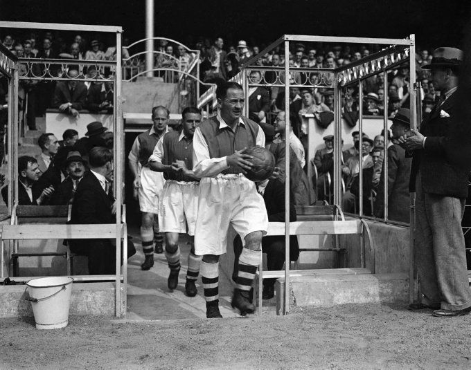 Soccer Alex James leads Arsenal out on to the Highbury pitch for the first game of the 1936/7 season against Everton.