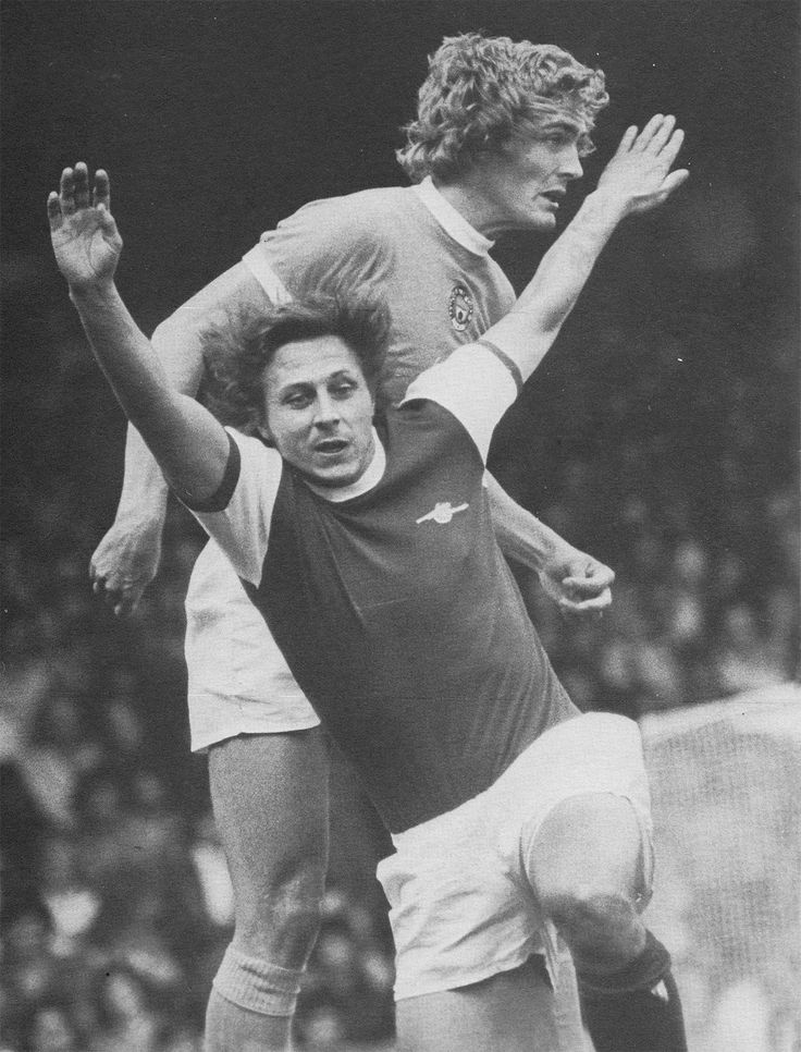 24th August 1974. Manchester City defender Colin Barrett out jumping Arsenal centre forward John Radford, at Highbury.