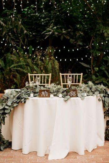 Mesa dos noivos decorada em greenery, com plaquinhas de madeira e decoração de luzinhas. #casamento #wedding #decoracaodecasamento #weddingdecor #stringlightswedding #bohowedding