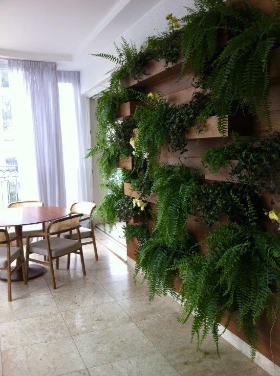 ISABELA BICALHO , ANGELA TOVAR E KARLA FRANCESCHINI Muro verde com Prateleiras camufladas em ripas para suporte de vasos para melhor manutenção .