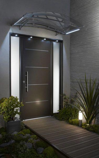 Style déco design devant la porte d'entrée noire de cette maison, soulignée par une allée en bois et de la verdure, judicieusement illuminé par des lumières d'extérieur