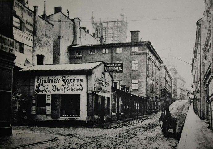 Hamngatan 1905. Till vänster Västra Trädgårdsgatan mynning. Sidenhuset byggdes på tomten till vänster och NK mittemot. Hörnet på huset man skymtar längst till vänster i bild är Blanchs Café. Foto. Stockholms Stadsmuseum.