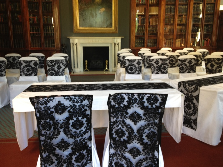 Black flocked organza chair veils and sashes on white chair covers in the Library at Rudding Park