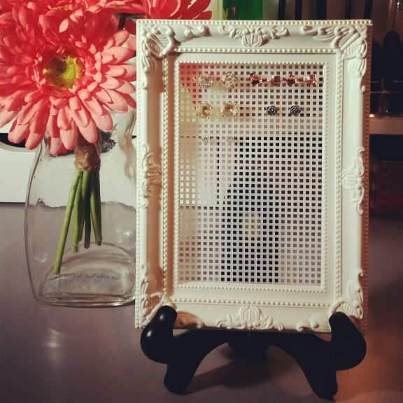 $5 DIY earring holder. Using: $1 picture frame (dollar store) $1 plastic canvas for sewing/knitting (craft store) $3 wooden easel (craft store) Optional: hot glue Remove glass and backing from frame. Cut plastic canvas to fit. Secure to frame using the tabs that held the frame backing. Hot glue can be used to glue plastic canvas to frame for a sturdier hold. Place frame on easel. Add earrings. :) Optional: Frame can be painted to desired color before adding plastic canvas.