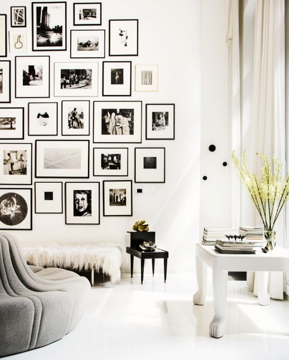 Gallery wall: black and white photography prints in frames; white floor, white walls, white curtains, white coffee table